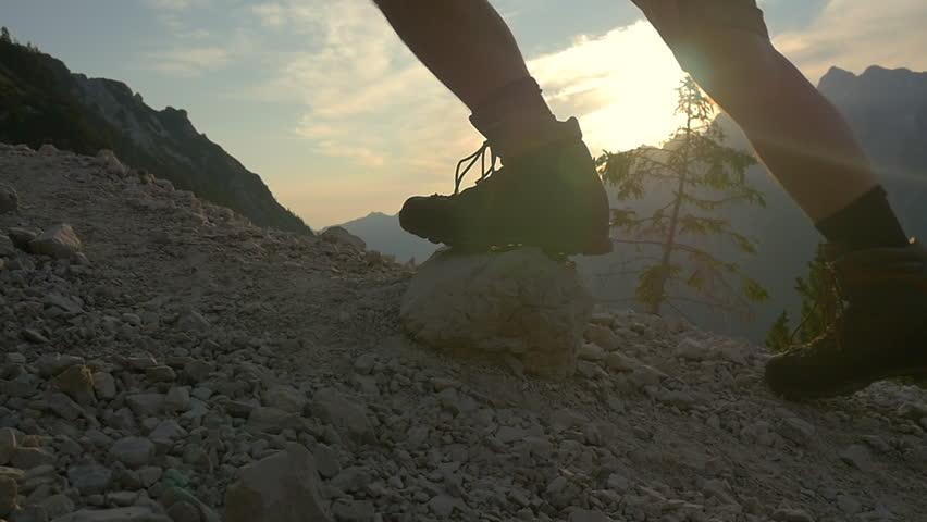 SLOW MOTION: Hiking uphill in the mountains at sunrise closeup