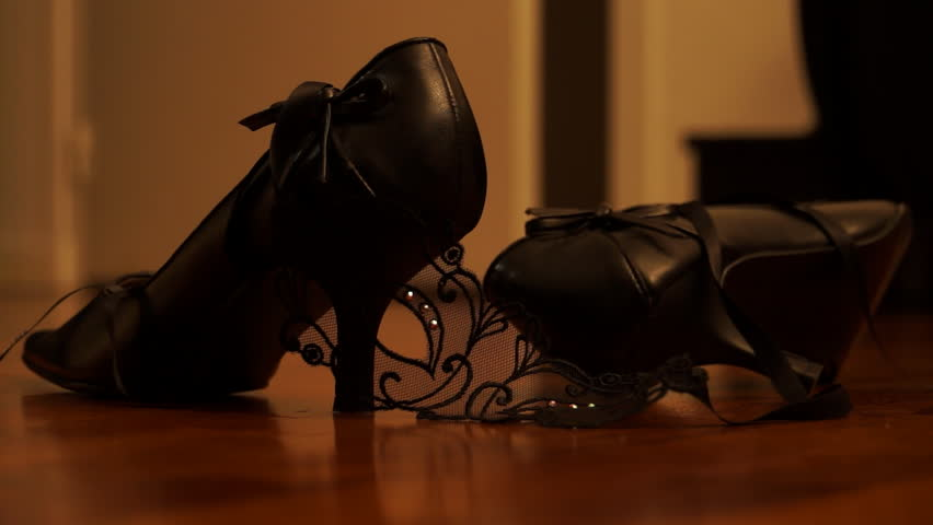 Handcuffs thrown on wood floor near black high heels. Orange cast. Sensual ambiance. Erotic atmosphere. Sexual game.