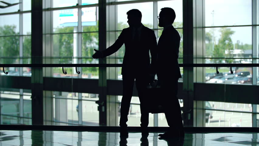 Silhouettes of two businessmen greeting each other with a handshake