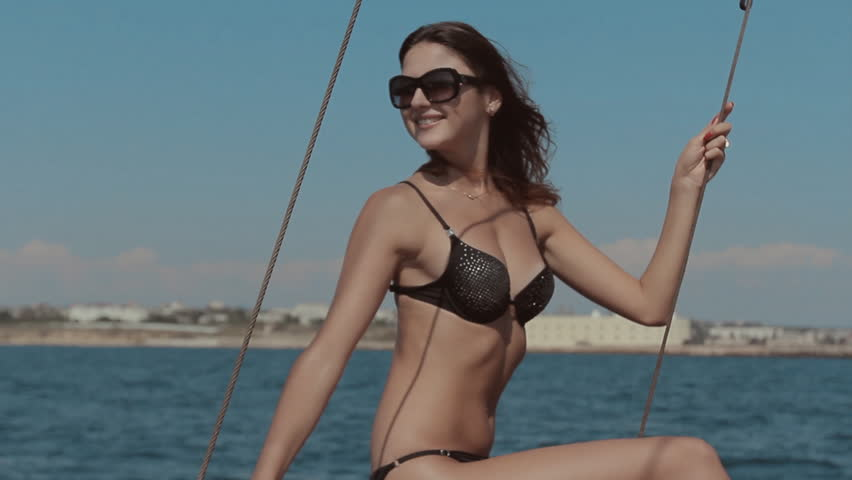 Skinny girl in a bikini and sunglasses sitting on the edge of the yacht  among the sea