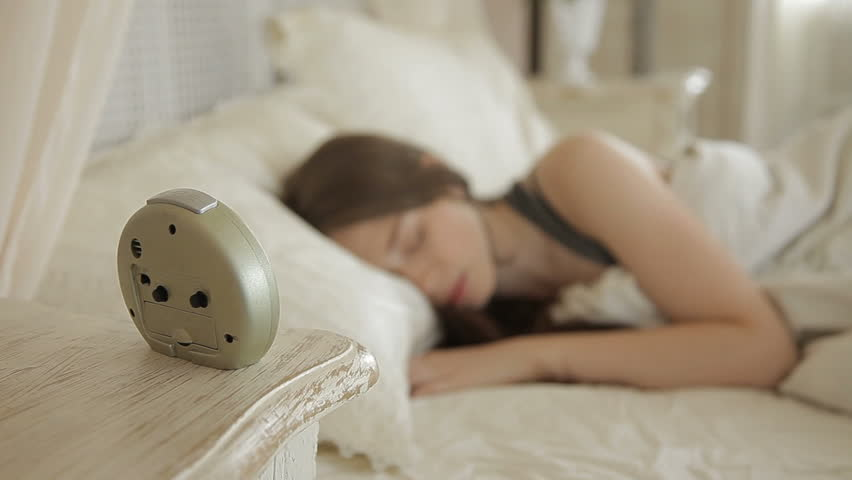 Beautiful young woman turns off the alarm clock, wakes up and quickly gets out of bed. Overslept!
