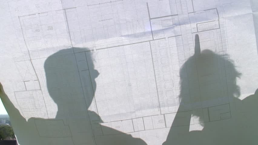 HD 1080i: Shadows of two people on a construction plan discussing. Tripod.