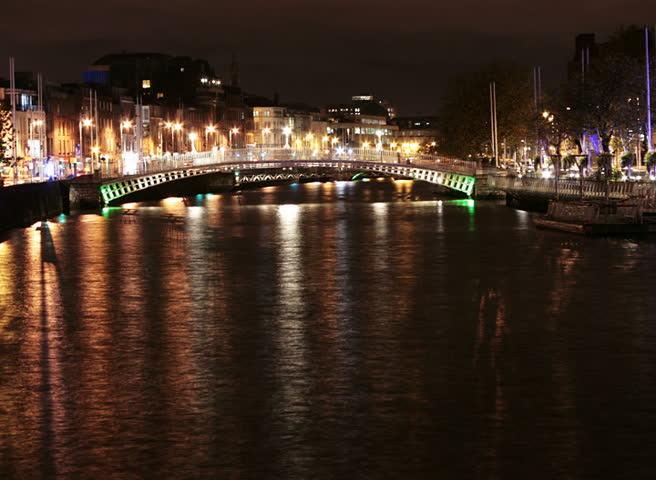 Time lapse of river Liffey banks with Ha'penny bridge in the background, at night in Dublin city, Ireland