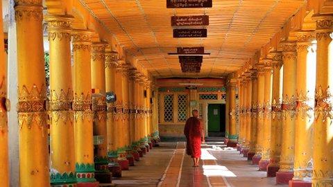 Monk in traditional dress in walkway Kha Khat Wain, Kyaung Monastery, Bago, Asia