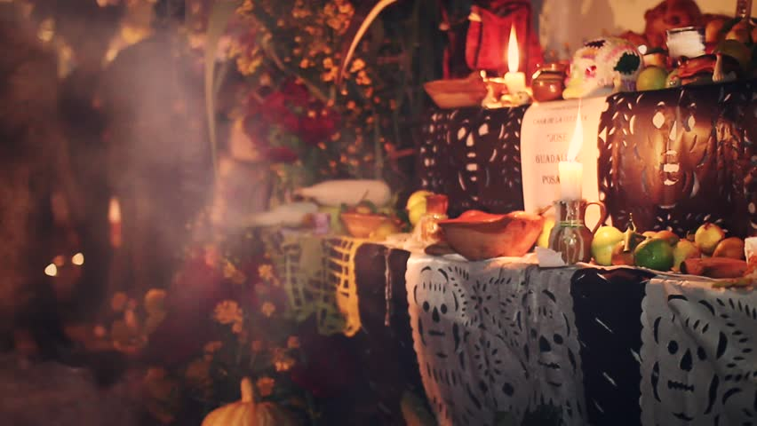 Day of the dead offering altar with bread ¨Pan de Muerto¨ chocolate and amaranto skulls, flowers and smoke