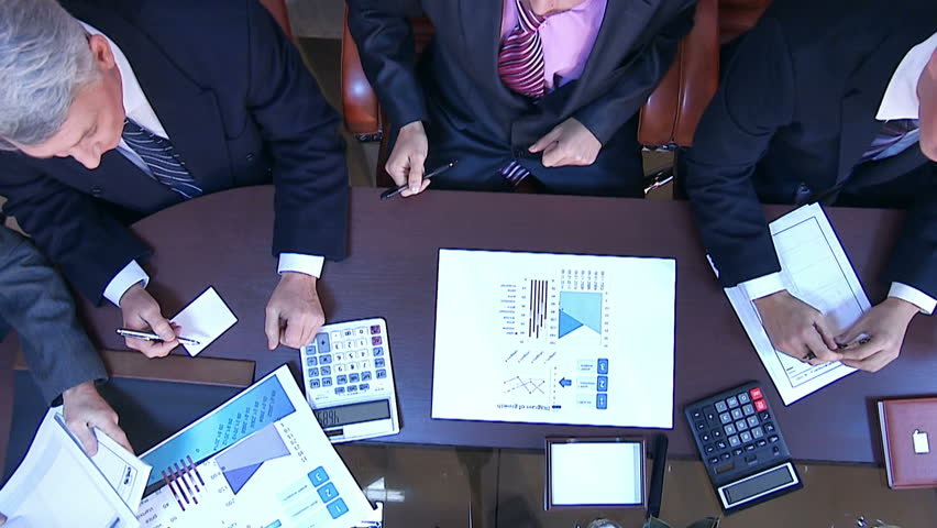View from above. Several business people working with business papers. Graphics and drawings. See as well the hands of other people bringing documents and other business accessories | Shutterstock HD Video #7714393