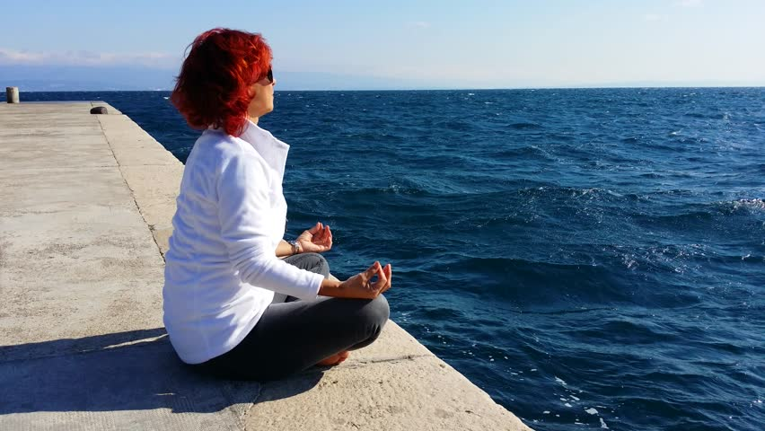 Pretty middle aged woman meditating, performing joga on sea coast, windy sunny day,high,rough sea in the background, 4K, 3840x2160, 2160p, high resolution video with sounds of wind and breaking waves | Shutterstock HD Video #7733863