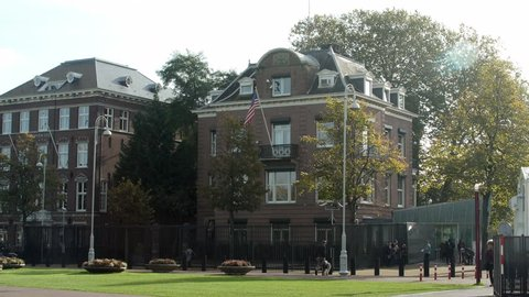 Wide shot of the US Consulate with US flag in Amsterdam. People walk by.