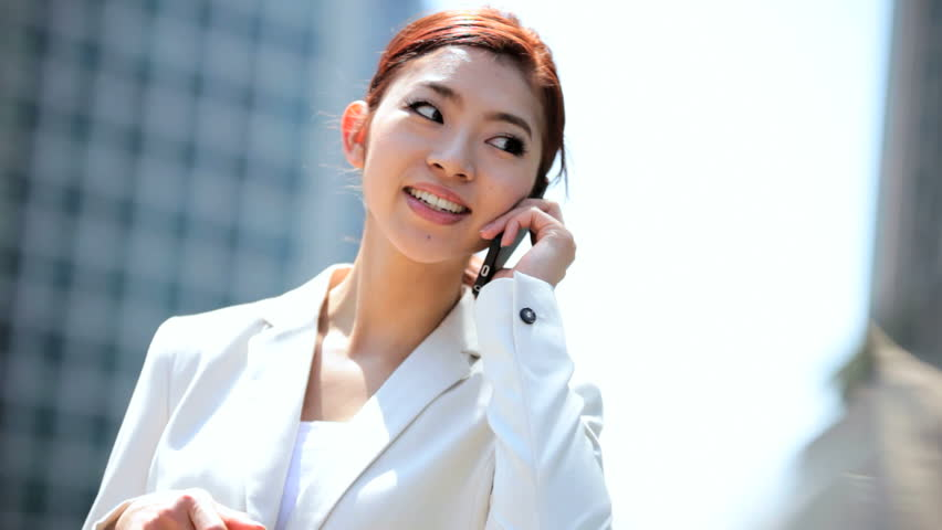 Female ethnic Asian Japanese corporate business executive outdoors city downtown offices WiFi hotspot smart phone device
