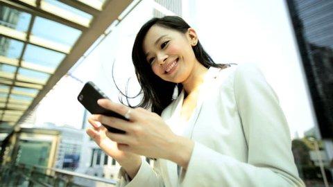 Downtown buildings Hong Kong Asian Chinese ethnic woman smart business suit wireless hotspot cloud technology smart phone