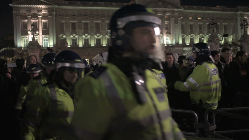 LONDON, UK - NOV 5: Riot Police officers wearing helmets are surrounded by protesters chanting 'Shame on You' during the Million Masks March in front of Buckingham Palace in London on November 5, 2014
