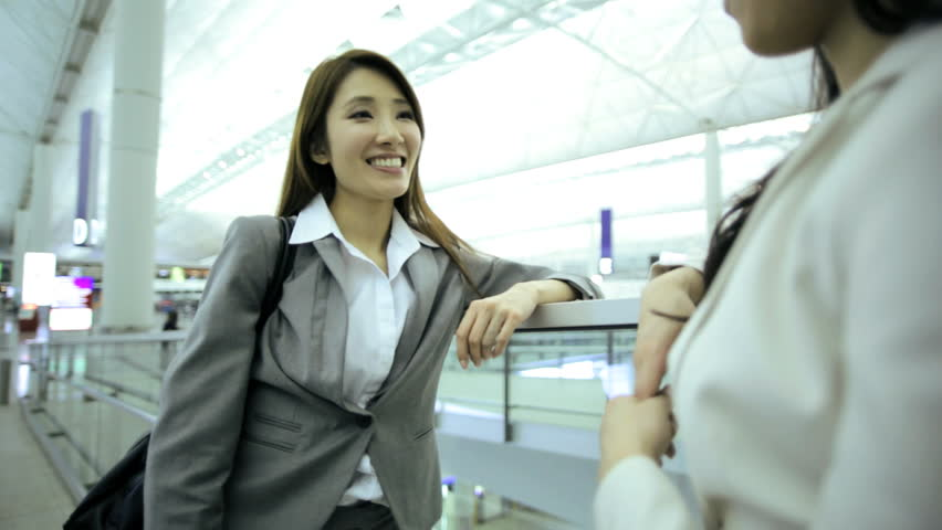 Two female Asian Chinese brunette businesswomen consultant airport departures hall travel destination professional corporate executive meeting | Shutterstock HD Video #7854169