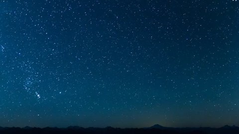 A Time lapse scene of stars moving across the sky with Glacier Peak in the distance.    On the left, the Pleiades Constellation can be seen rising into the sky.