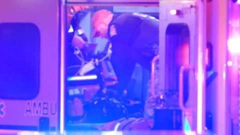 Montreal, Canada - October 2014 - 4K UHD - Police officer doing chest compression CPR in back of ambulance at night