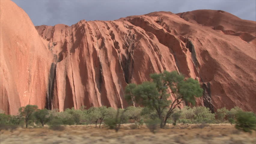 PR available - image approved for commercial use by Park authorities. Uluru - Ayers Rock. Aboriginal sacred place. UNESO world heritage. Sun is color painting red sandstone rock. Dolly left to right.