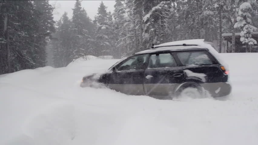 Haines, AK - Dec 2013: Close handheld shot of a Subaru Outback or Forester plowing through fresh snow on an Alaskan road during a blizzard.