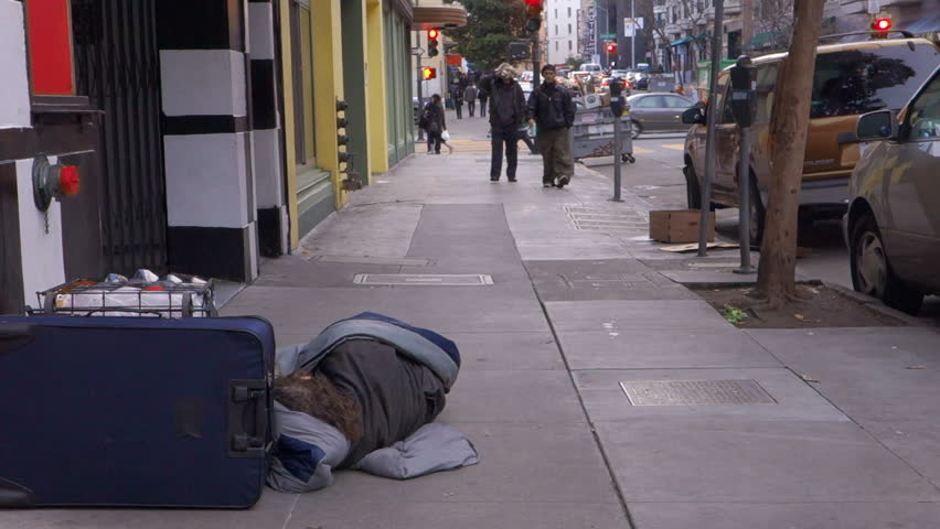 San Francisco, CA - 2014: People on sidewalk approach and pass a homeless person asleep on the sidewalk.