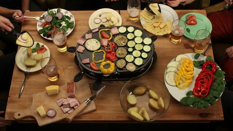 Raclette grill party top view - eating grilled vegetable & drinking beer with friends - time-lapse, 4K, (also available as closeup shot from another angle)