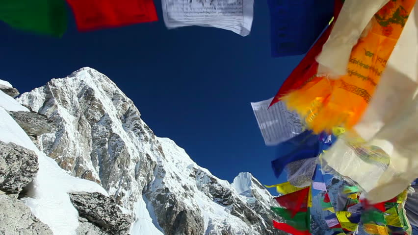 Buddhist colorful prayer flags blow by the wind in the mountains in Himalayas, Nepal.