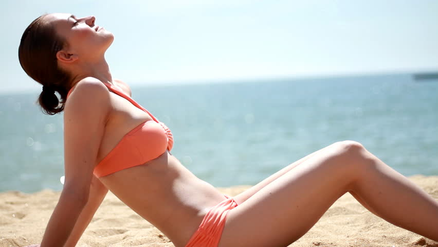 Young woman on the beach during sunbath