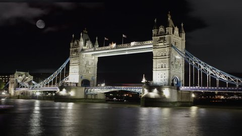 Time-lapse footage of London's Tower Bridge shot on a cold winter evening.  A misty, foggy moon shadows the scene. The bridge opens its gates twice as passing ships roll in along the Thames river.