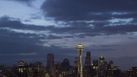 Sunrise lights up the clouds over Seattle as the lights of the city fade away.
