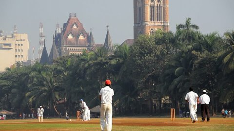 INDIA - DECEMBER 2012: Team of cricketers playing a cricket match on the Oval Maidan in Mumbai, India