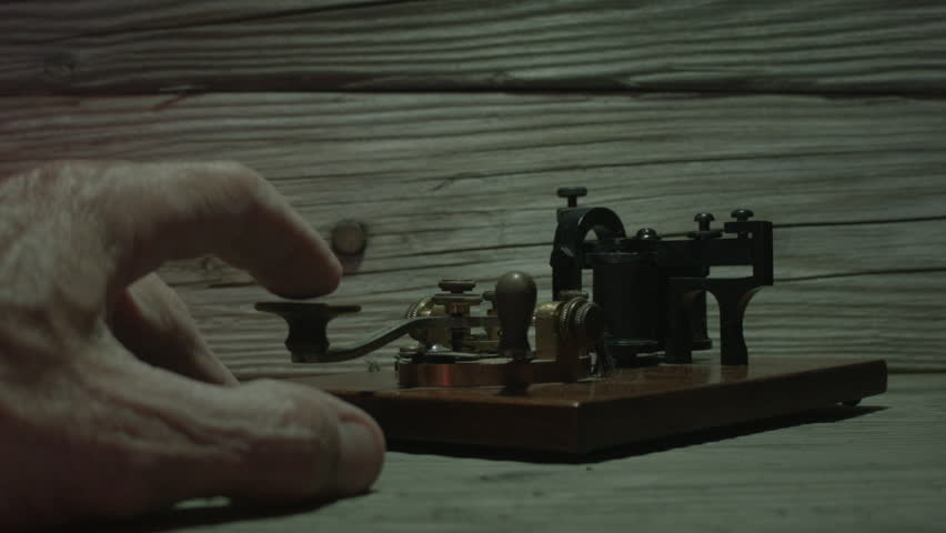 MORSE CODE KEY ON AN OLD WOODEN TABLE. OVERHEAD SHOT AS A HAND SENDS A MORSE CODE MESSAGE. WORKING MECHANISM. SPARK VISIBLE.