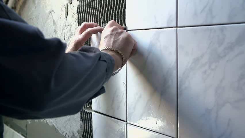 Ceramist puts tile on the wall. Professional ceramist is laying big grey ceramic tile on the wall full of other ceramic tiles