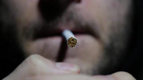 Slow motion, super close up shots of a man smoking a cigarette blowing smoke. Macro. 96fps.