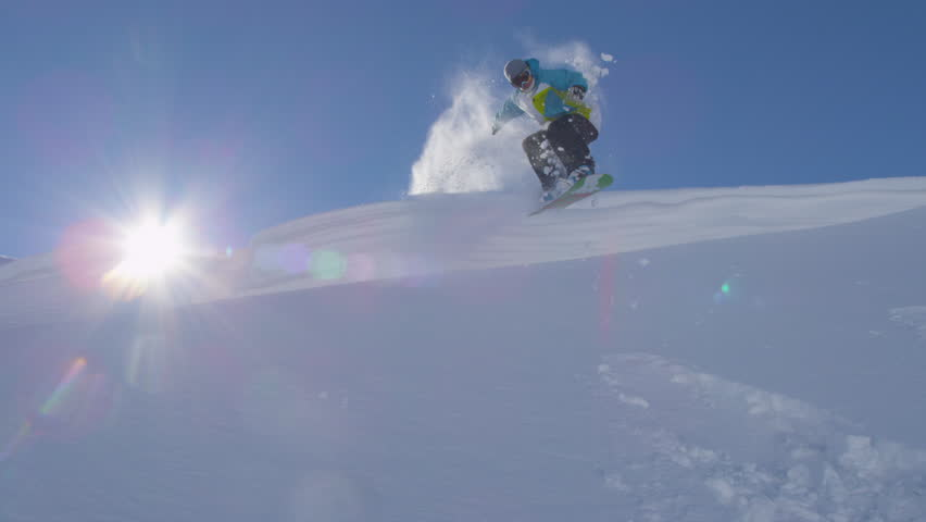 SLOW MOTION: Snowboarder jumping over the powder cliff #8053513