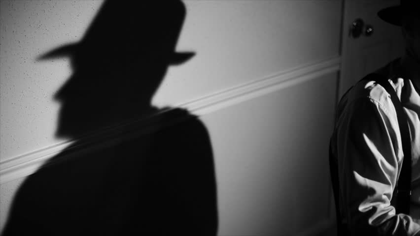 The camera pans from a stark shadow of a person to a man wearing a fedora and typing on a vintage 40's typewriter. Film Noir,