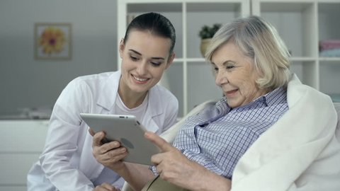 Close up of senior woman wrapped in plaid using digital tab assisted by young nurse