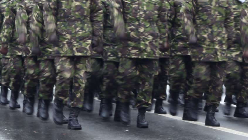 Soldiers marching in cadence at an army parade on wet road
