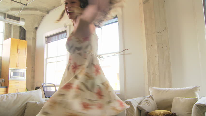 Woman in dress dancing while listening to headphones