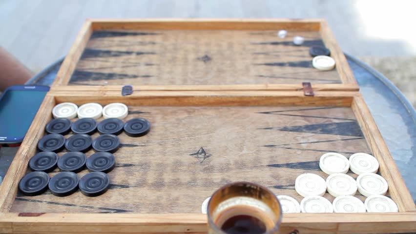 Two man playing backgammon outside