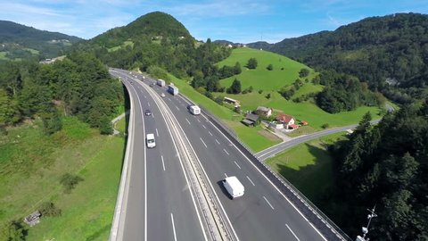 Highway road traffic on a bridge in a valley . Aerial shoot of a highway road with traffic cars and trucks in a valley with green grass field and trees in nature full of small hills