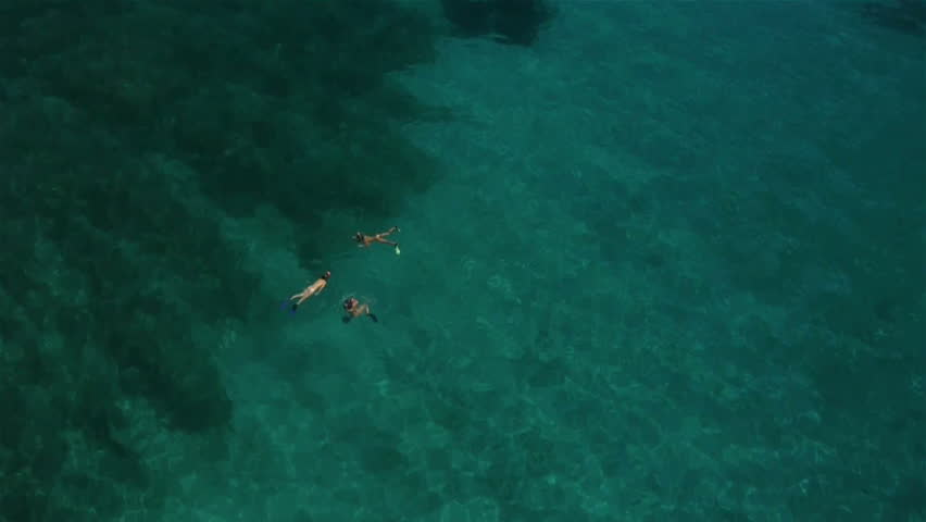 Aerial view and zoom out of diving girls into clear sea water on a shore #8198893