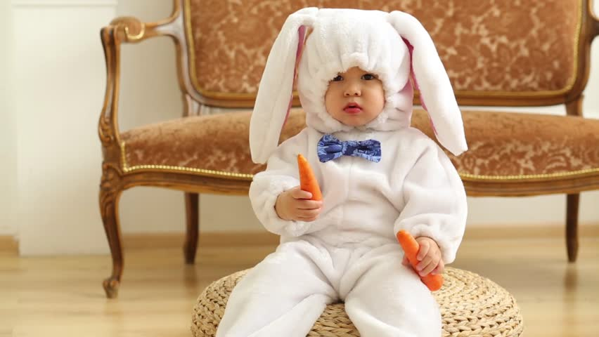 Baby boy in white costume of rabbit sits and holds carrot