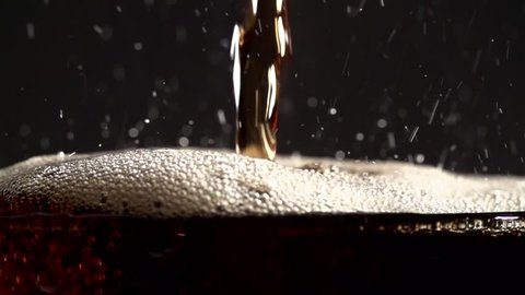 Cola is pouring into the glass with bubbles in macro slow motion.