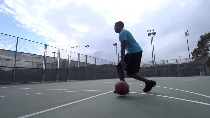 A young man playing basketball on a rainy day. - Super Slow Motion - Model Released - 1920x1080 - HD - filmed at 240 fps #8230483