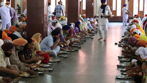 AMRITSAR, INDIA - SEPTEMBER 26, 2014: Unidentified poor indian people eating free food at a soup kitchen in the Golden Temple