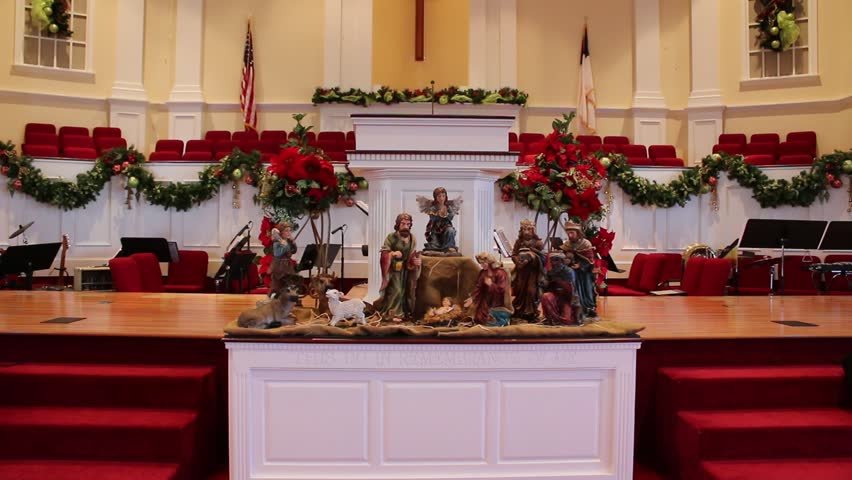 zoom in on nativity scene inside of church decorated for christmas