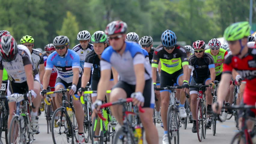 VRHNIKA, SLOVENIA - JUNE 2014: Big group of professional cyclist passing the camera. Bicycle competition with cyclist speeding after start. Close up on competitors with helmets and professional bikes. | Shutterstock HD Video #8262445