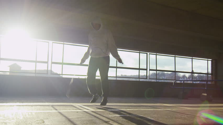 4K Slow motion tracking shot of a man jump roping in an urban environment during the day with sun flare, shot on RED EPIC #8332213