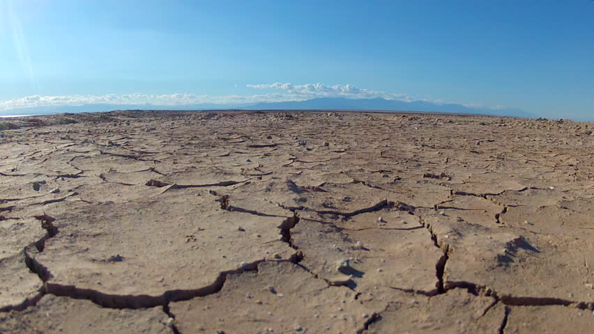 Close up zoom shot of cracks in the mud of a dried up lake bed. Drought conditions and lack of water and precipitation has led to many lakes drying up. | Shutterstock HD Video #8336233