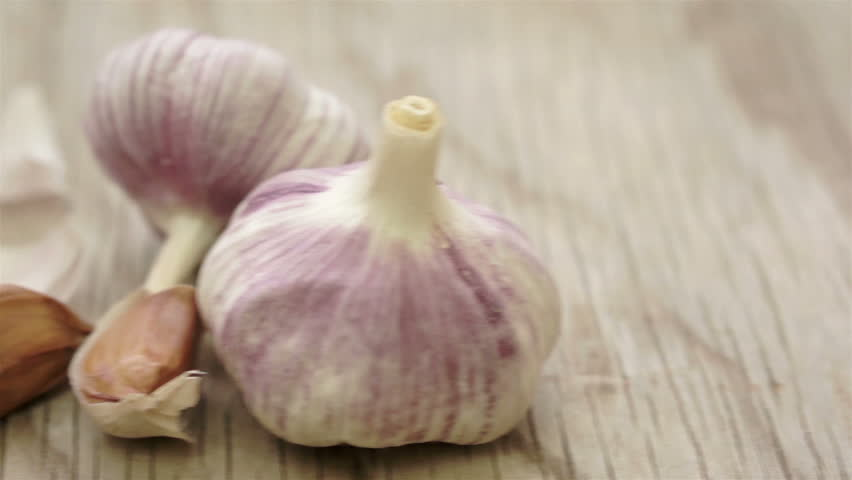 Close up dolly shot of whole garlic bulbs and a few cloves of garlic on an old wooden table or background.