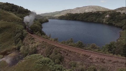 GLENFINNAN, SCOTLAND - JUNE 2014: Aerial shot of the Jacobite Steam Train passing a loch in the Scottish highlands en route to Fort William