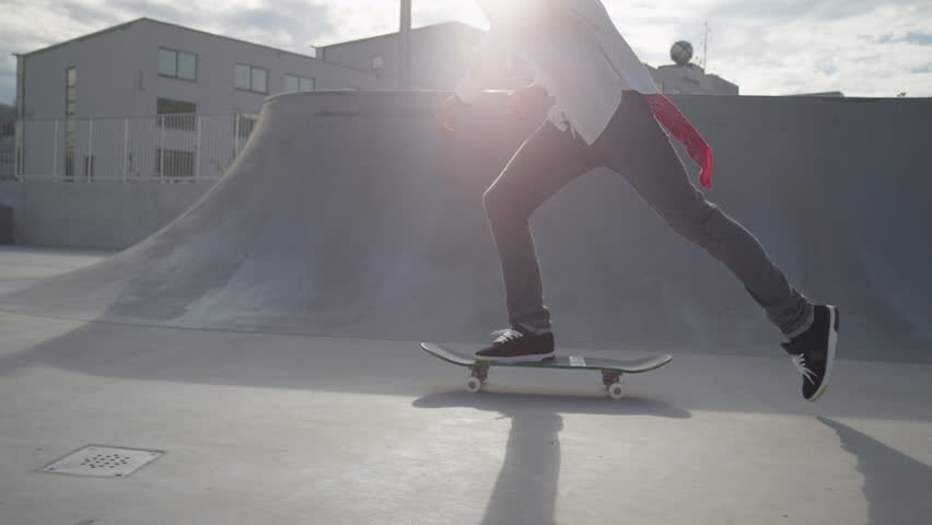 SLOW MOTION: Skateboarder riding and jumping in a skate park