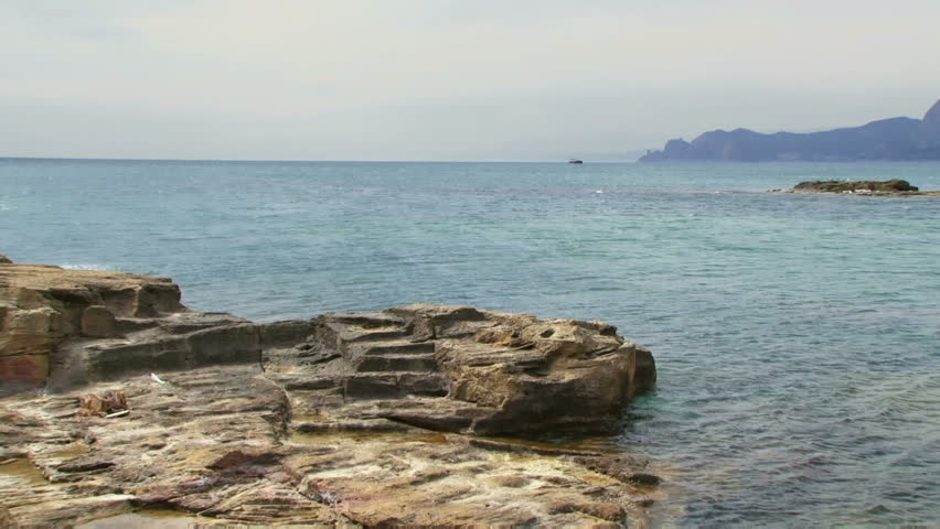 Rocks In Spanish Part - 21: Couples Walk On The Rocks. A Young Couple Goes On A Rock Against The Sea